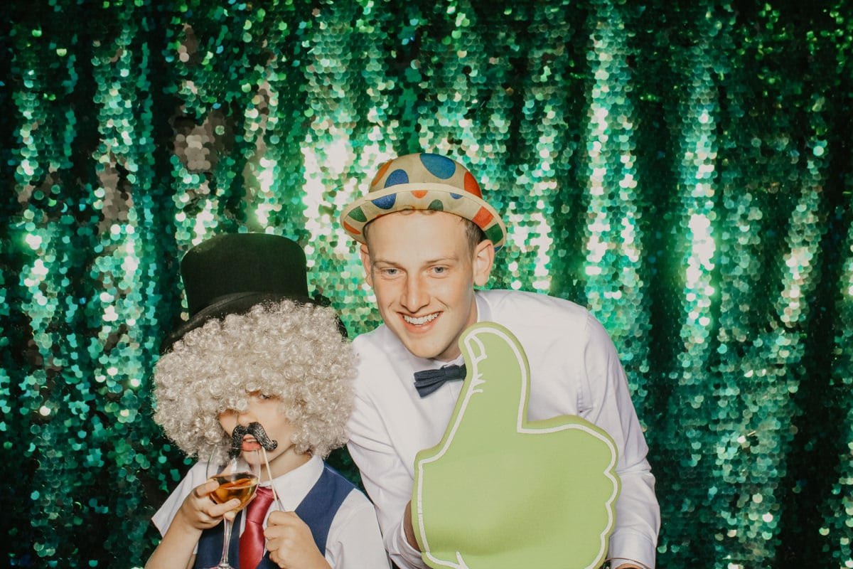 groom and guest posing in front of green sequins backdrop for a barn wedding