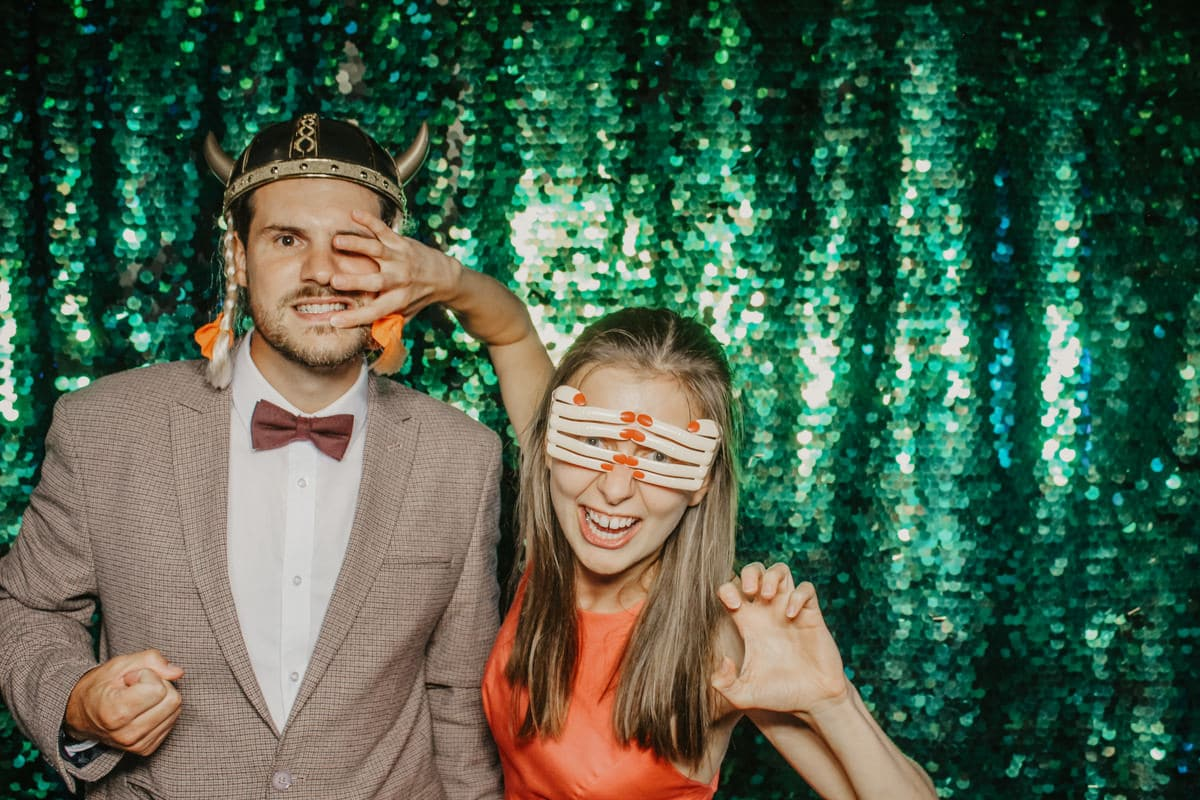couple posing with mad hat photo booth props in front of the green sequins backdrop