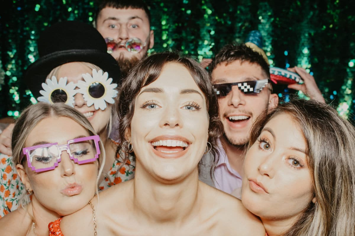 big group of people posing in front of a green sequins backdrop during a barn wedding Gloucestershire