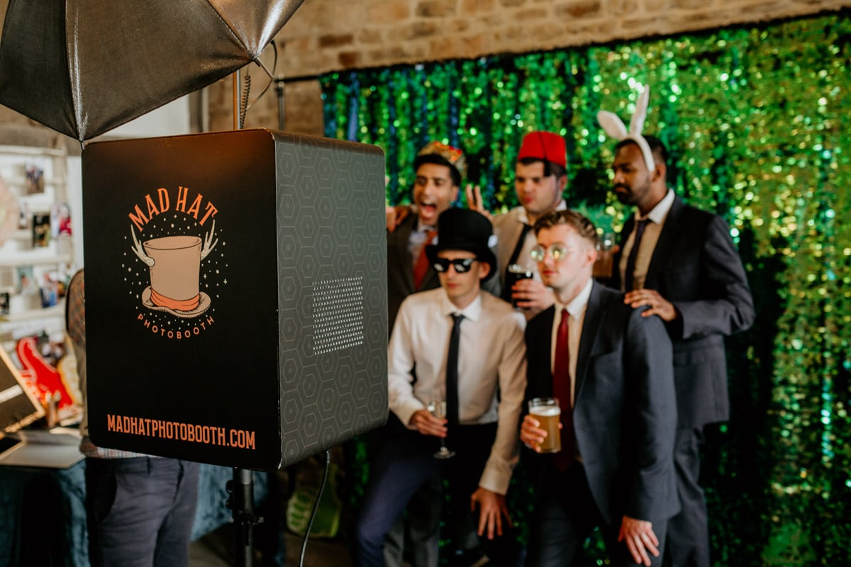 mad hat photo booth during a barn wedding reception with guests posing in front of sequins backdrop