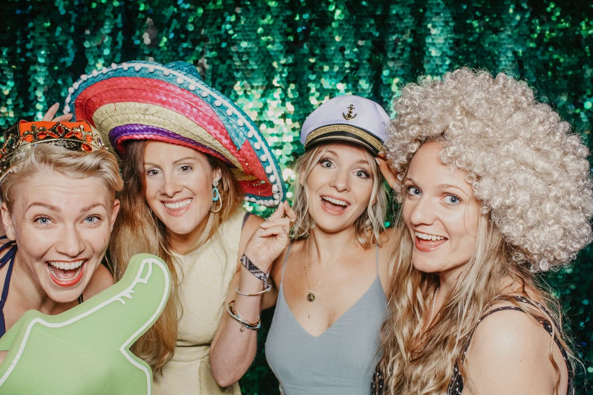 group of ladies posing with a green sequins backdrop for mad hat photo booth props during the wedding reception at Priors Court Barn Gloucestershire