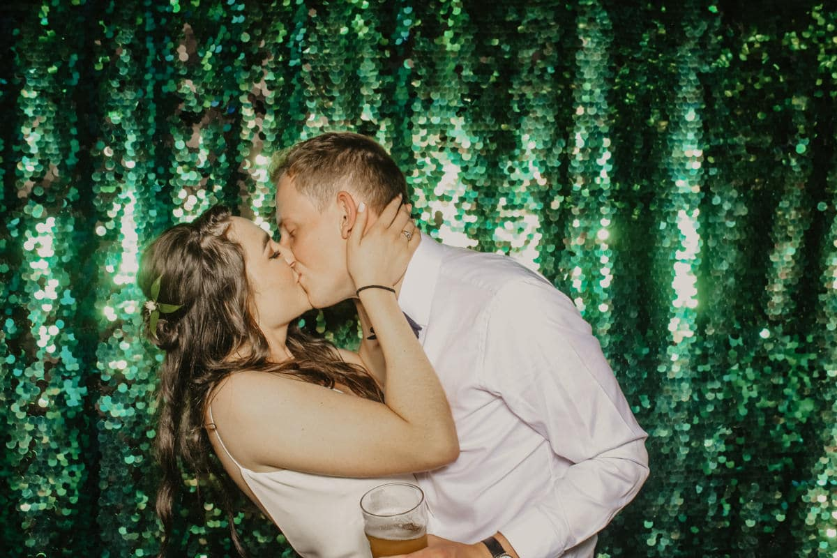 bride and groom kissing during the wedding reception at Priors Court Barn in Gloucestershire