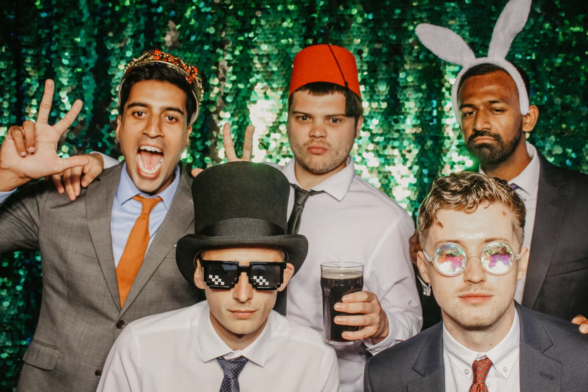 Group of guys posing with props during the mad hat photo booth wedding entertainment in Gloucestershire
