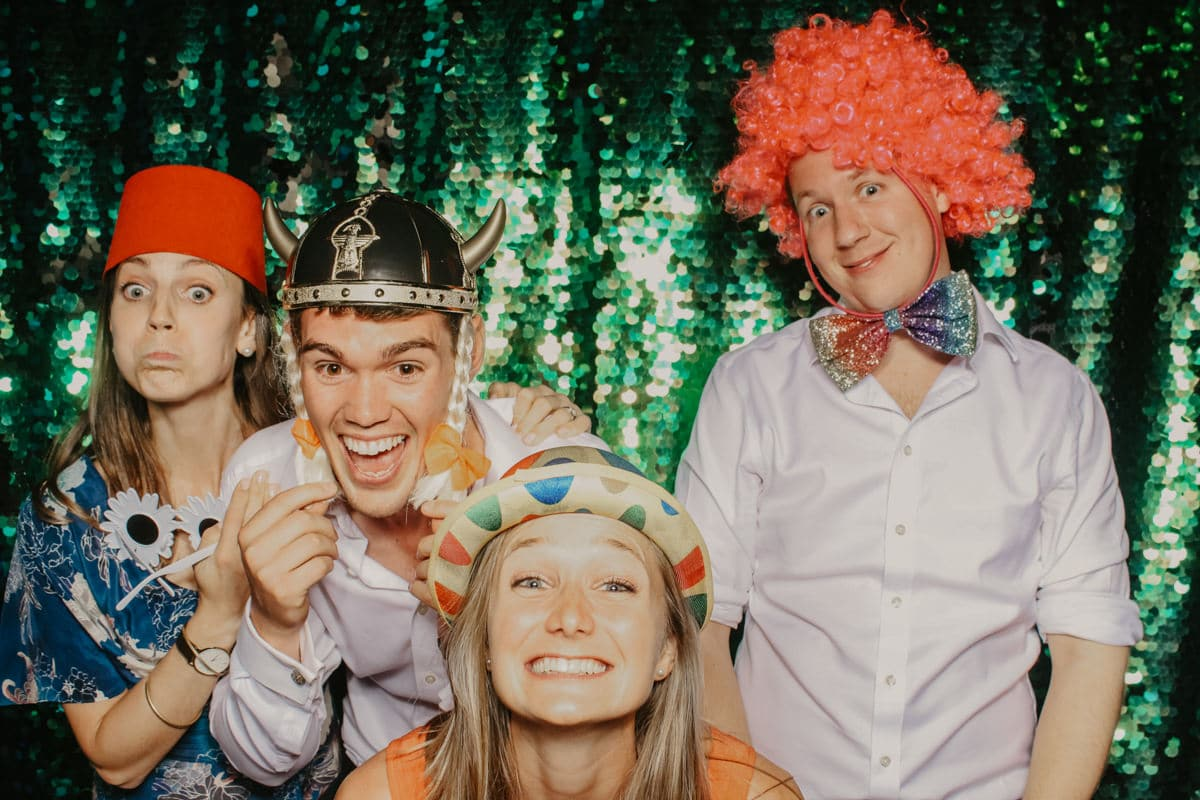 people having fun with mad hat photo booth during a barn wedding at Priors Court Barn in Gloucestershire