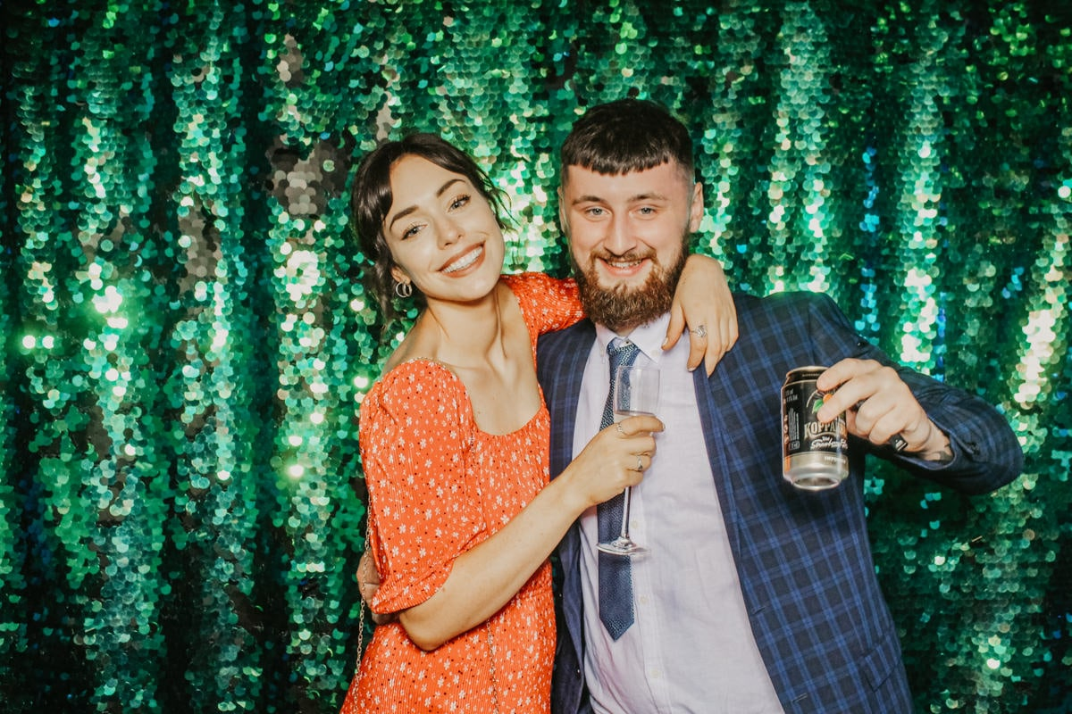 couple posing in front of green sequins backdrop during a barn wedding in Gloucestershire