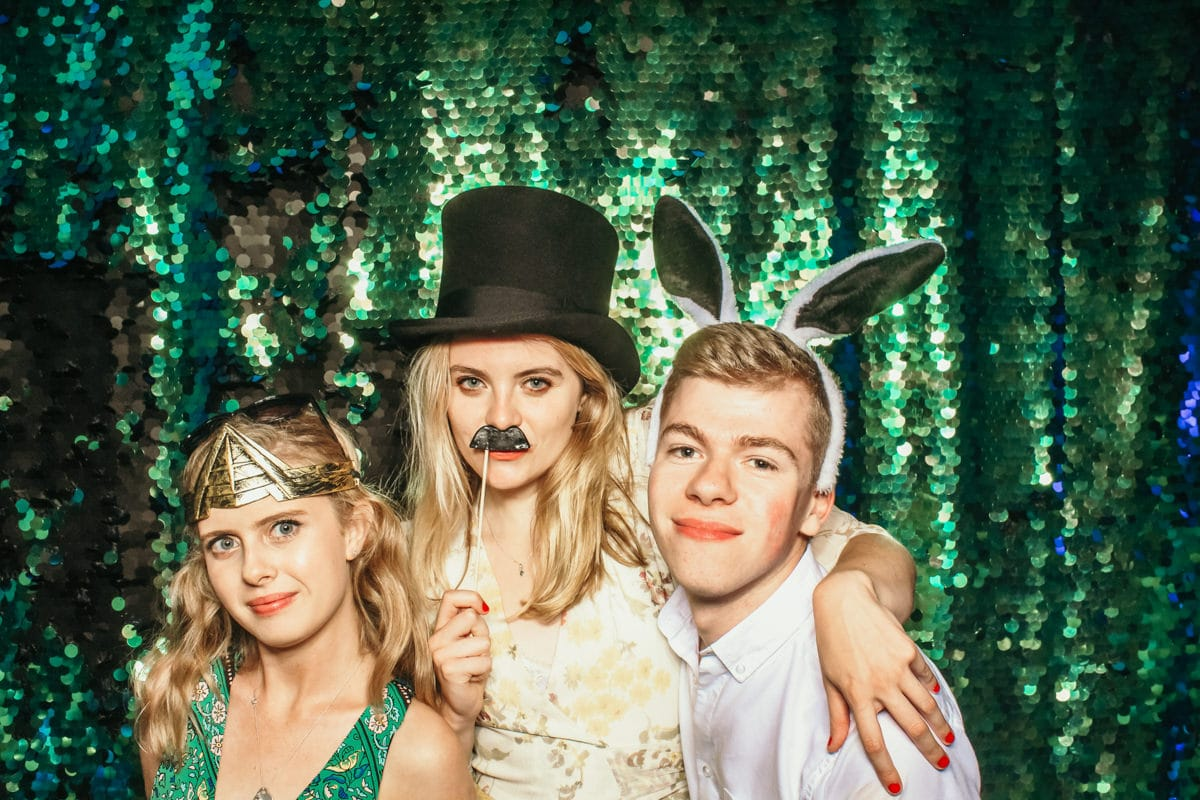 friends having fun with a photo booth in the cotswolds for a birthday party