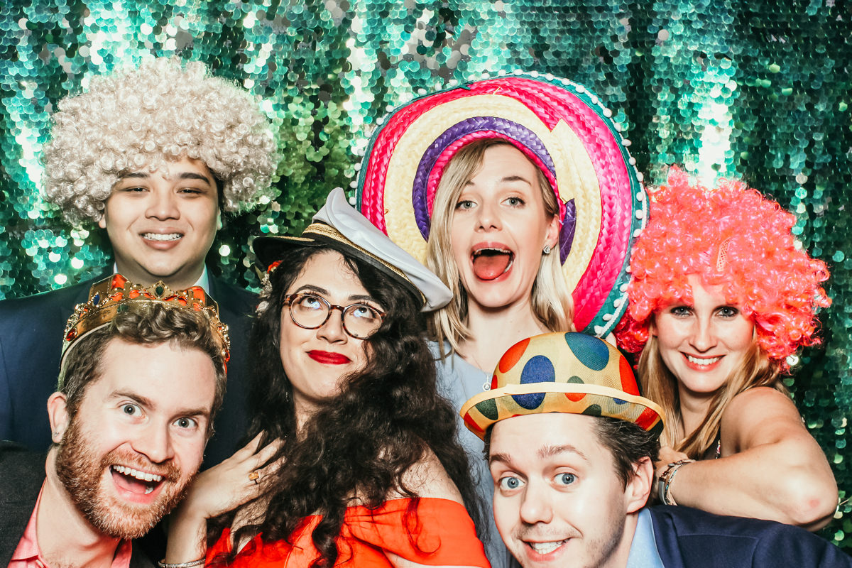 group of guests at a wedding posing with wigs and hats in front of a green sequins backdrop at Elmore Court wedding venue