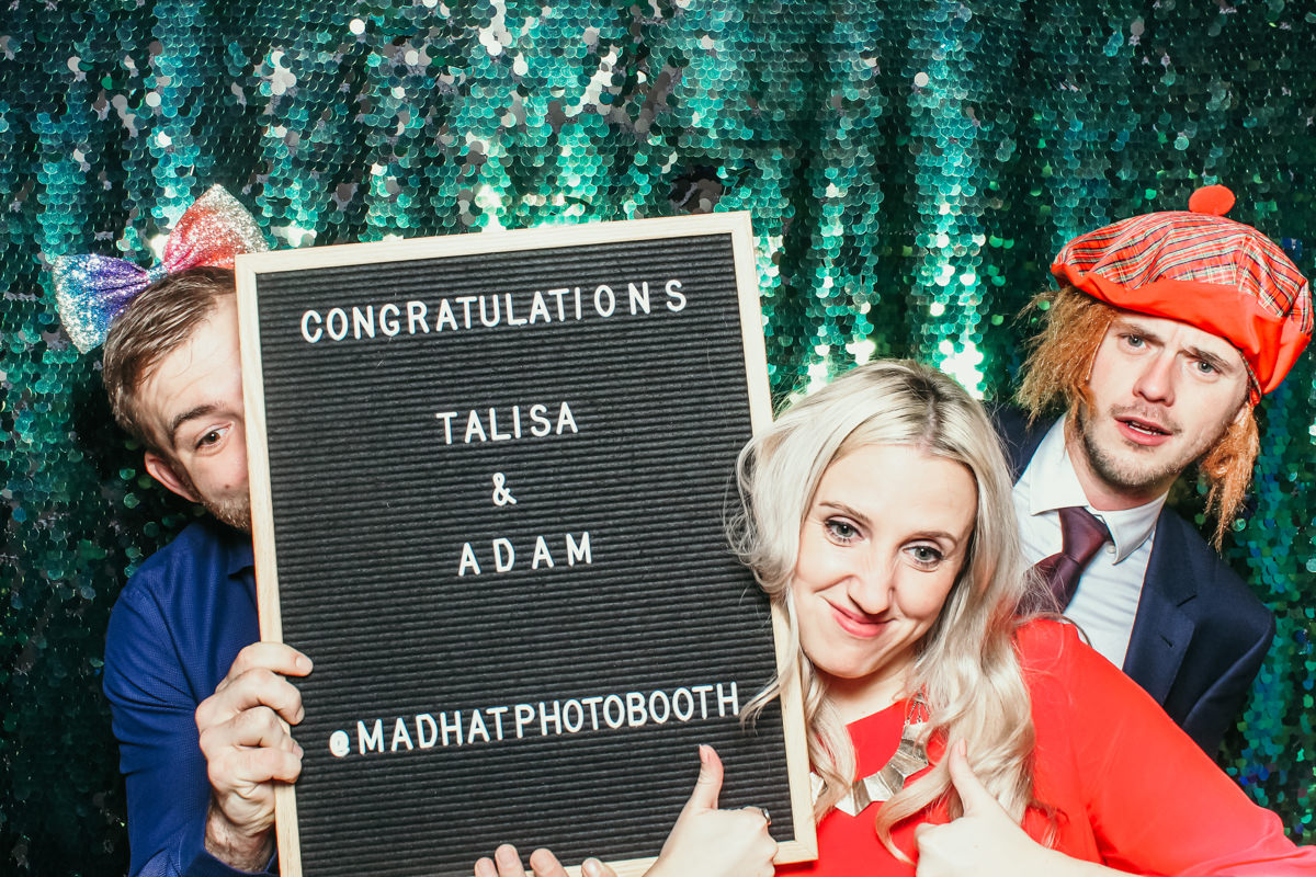 guests posing for a photo booth at elmore court, holding the letters board by mad hat photo booth