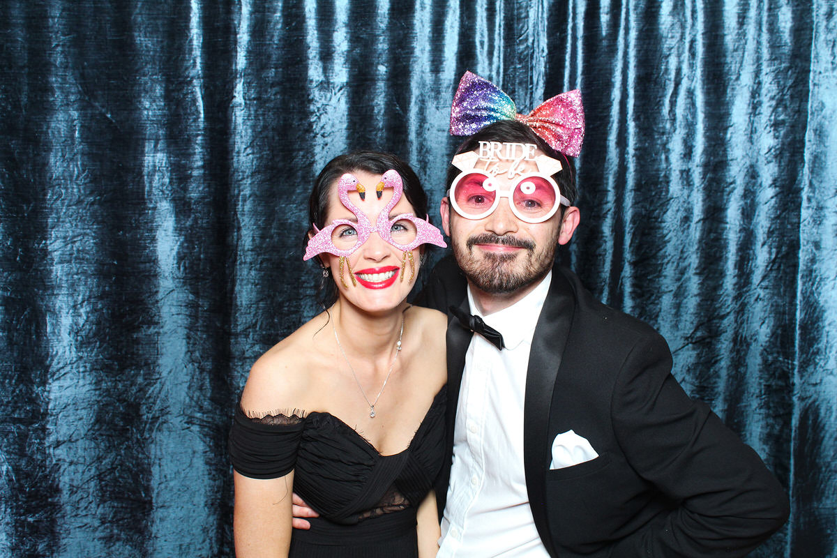 couple wearing props with a velvet blue backdrop for a cotswolds photo booth event